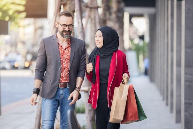 Heureuse femme musulmane et garçon avec la main de shopping de la ville tenant des sacs en papier