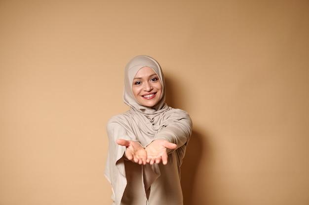 Heureuse femme musulmane en hijab et tenue stricte sourit gentiment et étend ses mains à la caméra en se tenant debout sur un beige