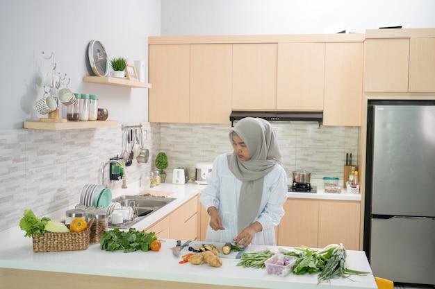 Heureuse femme musulmane préparant le dîner de l'iftar dans la cuisine seule
