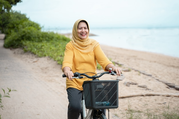 Heureuse femme musulmane senior, faire du vélo