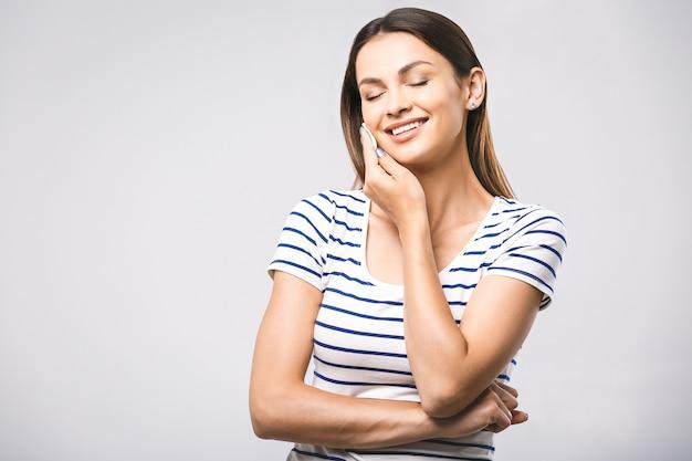 Heureuse femme nettoyant son visage avec des cotons