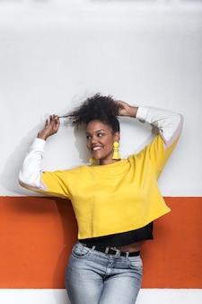 Heureuse femme noire aux cheveux bouclés en tenue tendance