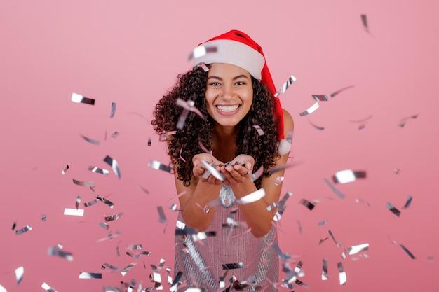 Heureuse femme noire avec des confettis volant dans les airs, portant bonnet de noel isolé sur rose