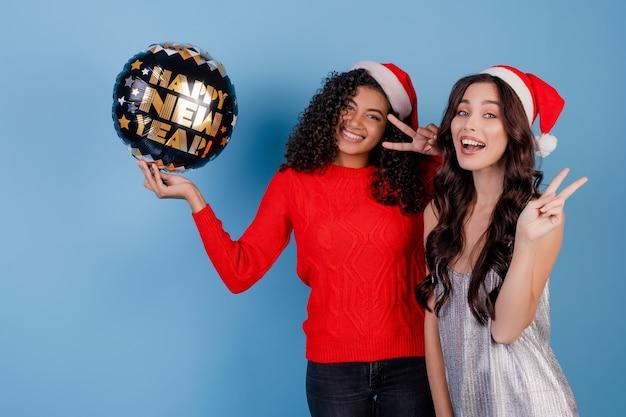 Heureuse femme noire et dame caucasienne avec ballon de bonne année et chapeaux de noël isolés sur bleu