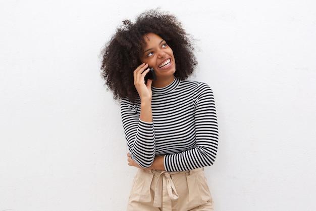 Heureuse femme noire parlant au téléphone mobile
