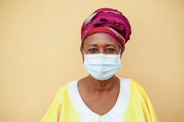 Heureuse femme noire senior avec masque facial portant des vêtements traditionnels
