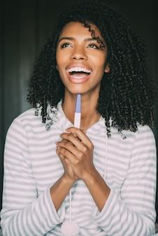 Heureuse femme noire avec un test de grossesse sur lit
