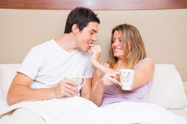 Heureuse femme nourrit un cookie à son petit ami assis sur un lit