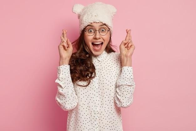 Heureuse femme optimiste croit sincèrement en la bonne fortune, prie pour le mieux, croise les doigts, porte des lunettes optiques, un couvre-chef et une chemise à pois, isolée sur un mur rose. faire un voeu