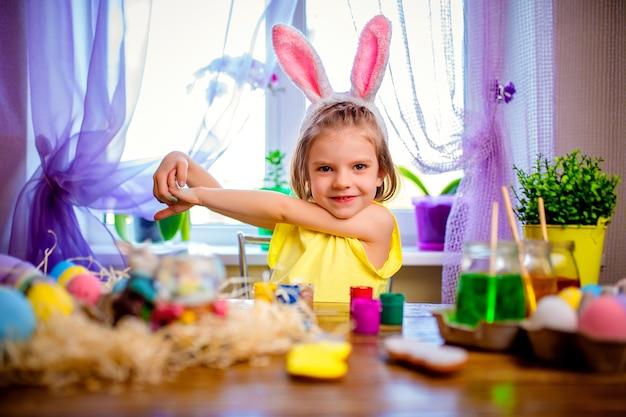 Heureuse femme de pâques dans les oreilles de lapin peignant des oeufs, petit enfant à la maison. vacances de printemps