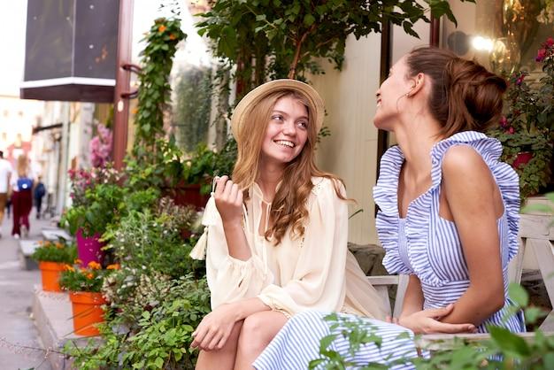 Heureuse femme parlant et riant dans un parc avec un fond vert