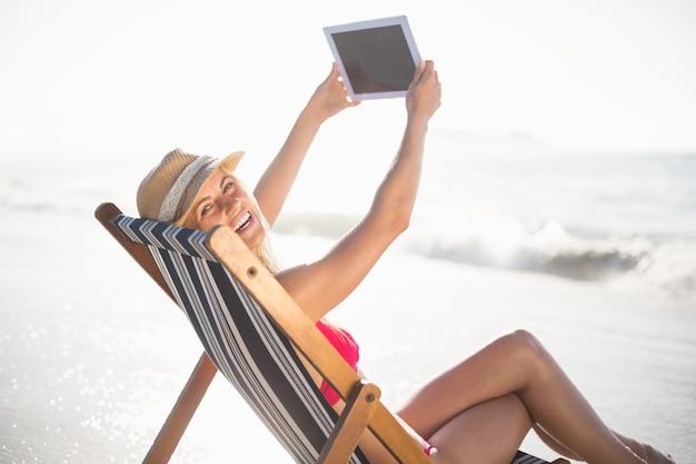 Heureuse femme parlant un selfie sur une tablette numérique