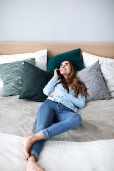 Heureuse femme parlant sur smartphone à la maison sur le lit. concept de personnes, de technologie et de communication.