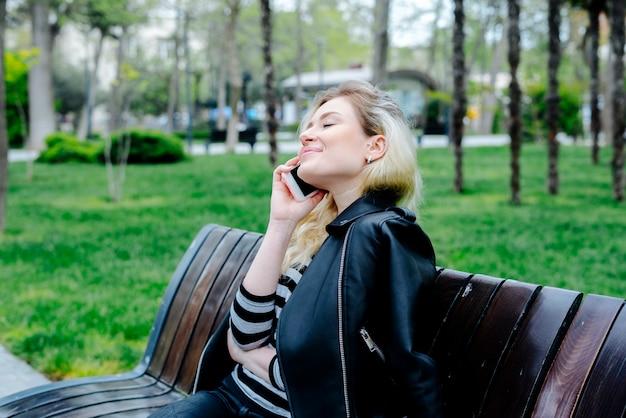Heureuse femme parlant sur téléphone mobile portant une veste en cuir noire et assis en plein air sur un banc