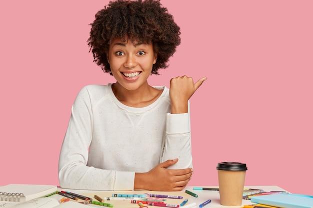 Heureuse femme à la peau foncée positive avec une coiffure afro, pointe de côté sur un espace libre pour votre publicité ou promotion, a une expression faciale joyeuse, aime le travail créatif, des modèles sur un mur rose
