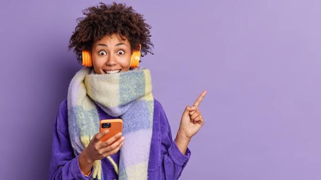 Heureuse femme à la peau sombre a les cheveux bouclés touffus enveloppés dans une écharpe d'hiver chaude tient un téléphone mobile pour la communication en ligne porte des écouteurs sur les oreilles surpris de voir des points d'offre incroyables sur la droite