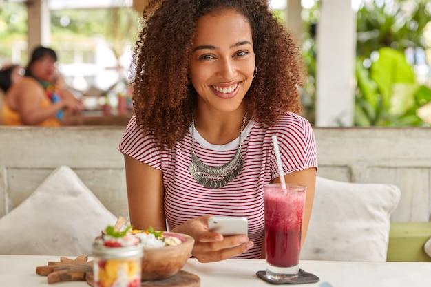 Heureuse femme à la peau sombre avec des cheveux croustillants, lit des nouvelles sur le site web, connectée à internet sans fil à la cafétéria, boit un smoothie frais, pose au restaurant en terrasse, installe l'application, porte un t-shirt, un collier