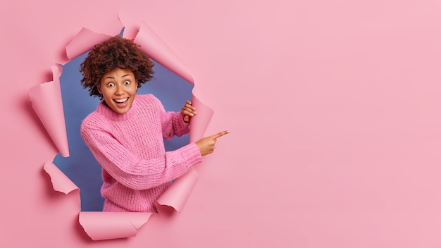 Heureuse femme à la peau sombre et joyeuse regarde avec une expression de surprise heureuse indique sur la droite montre l'espace de copie pour votre contenu promotionnel