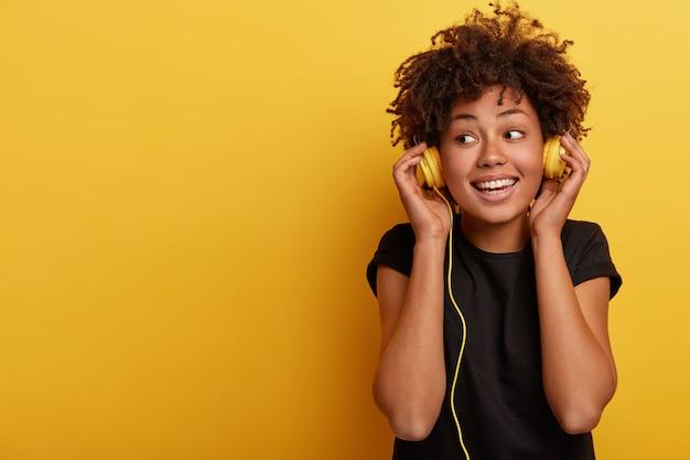 Heureuse femme à la peau sombre porte des écouteurs filaires, apprécie la bonne musique, regarde ailleurs, a le sourire à pleines dents