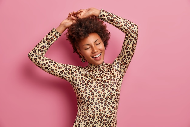 Heureuse femme à la peau sombre secoue le corps, lève les mains et danse sans soucis, porte un pull léopard, ferme les yeux