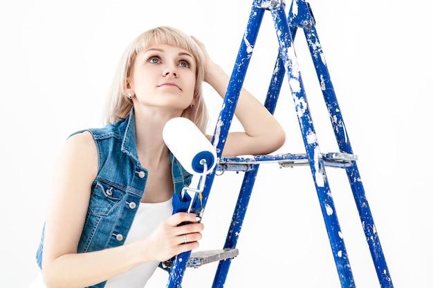 Heureuse femme peint mur avec rouleau à la maison