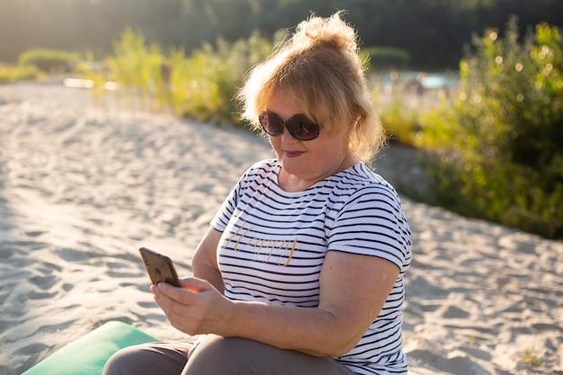 Heureuse femme plus âgée assise sur un sable et à l'aide de smartphone en plage d'été