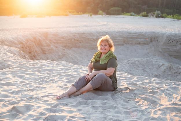 Heureuse femme plus âgée assise sur un sable à l'extérieur en été