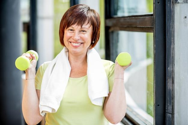 Heureuse femme plus âgée dans la formation de vêtements de sport avec des haltères à l'intérieur sur le fond de la fenêtre