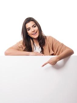 Heureuse femme pointant sur tableau blanc vide