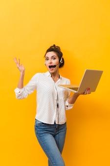 Heureuse femme portant un casque et tenant un ordinateur portable