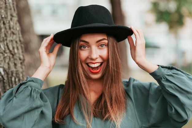 Heureuse femme portant un chapeau noir