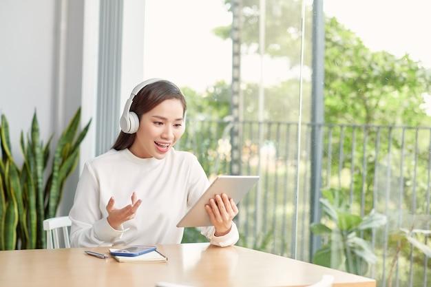 Heureuse femme portant des écouteurs sans fil agitant en vidéoconférence