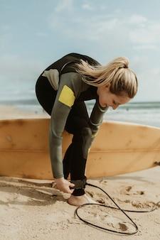 Heureuse femme portant une laisse de planche de surf