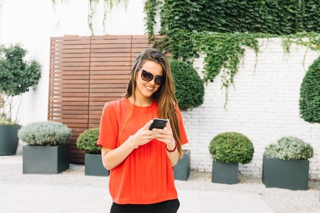 Heureuse femme portant des lunettes de soleil à l'aide d'un téléphone portable