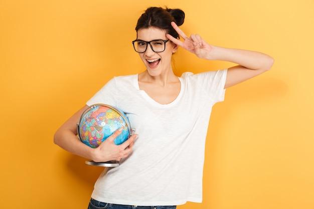 Heureuse femme portant des lunettes tenant le globe montrant le geste de la paix.
