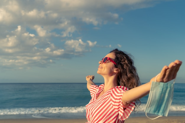 Heureuse femme portant un masque médical en plein air sur fond de ciel bleu. personne appréciant la mer en été.