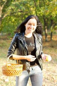 Heureuse femme portant un panier et une pomme marchant dans un parc.