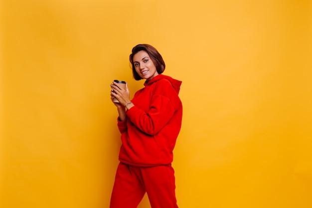 Heureuse femme portant des vêtements d'hiver chauds, un sweat à capuche et un pantalon, se réchauffe avec une tasse de café chaud
