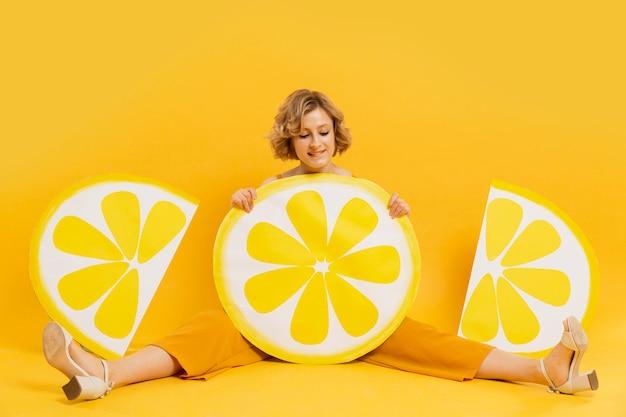 Heureuse femme posant avec un décor de tranches de citron