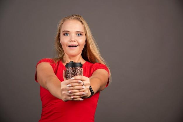 Heureuse femme posant avec du café à emporter sur un mur noir.