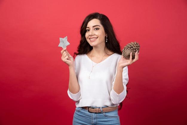 Heureuse femme posant avec une grosse pomme de pin de noël et une étoile sur fond rouge. photo de haute qualité
