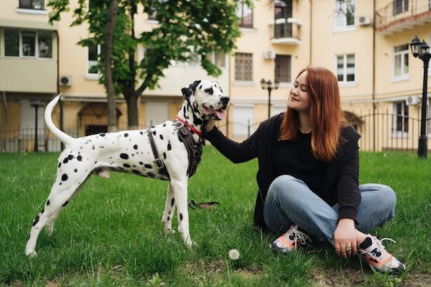 Heureuse femme posant et jouant avec son chien dalmatien assis dans l'herbe verte lors d'une promenade en ville