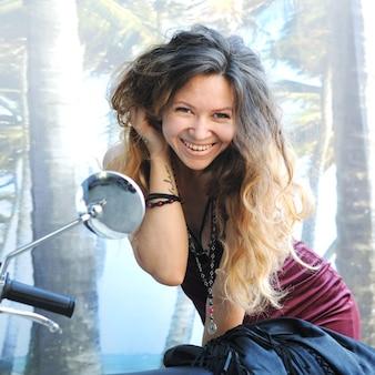 Heureuse femme posant avec moto, à l'extérieur