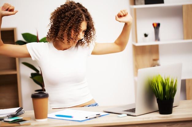 Heureuse femme positive avec des boucles sur la tête travaillant au bureau sur un ordinateur portable