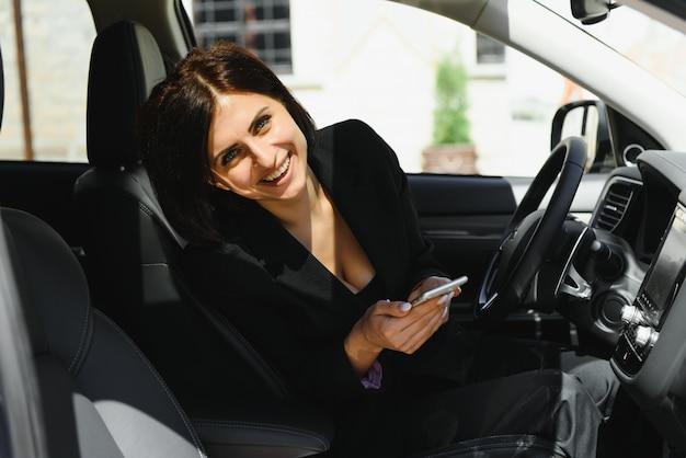 Heureuse femme positive souriant tout en utilisant le téléphone