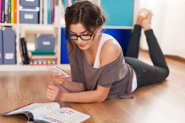 Heureuse femme prenant une photo du magazine par téléphone mobile