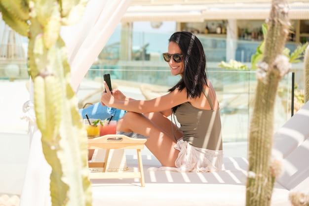 Heureuse femme prenant selfie sur lit à baldaquin pendant les vacances d'été