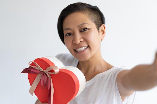 Heureuse femme prenant selfie photo avec boîte-cadeau en forme de coeur