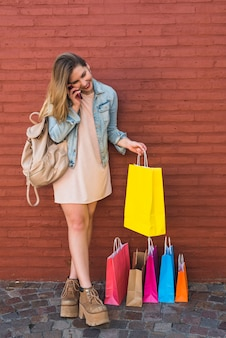 Heureuse femme près de sacs shopping lumineux parlant par téléphone