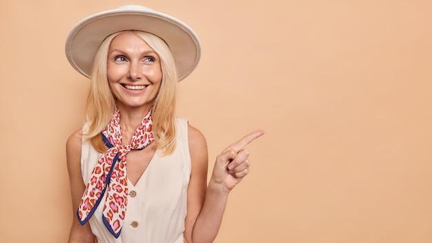 Heureuse femme de quarante ans en robe chapeau élégante et foulard sur le cou indique loin sur l'espace de copie annonce quelque chose montre le chemin du centre commercial isolé sur un mur marron